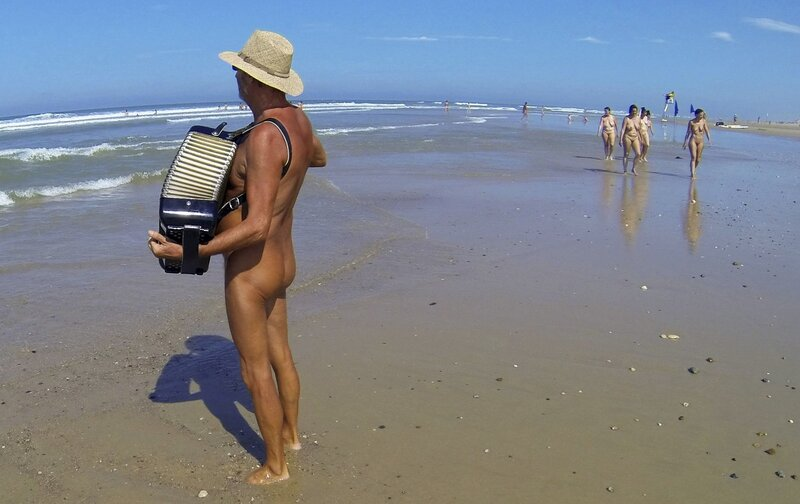 Jean-Pierre, a French naturist, plays the accordion on the beach at the Centre Helio-Marin naturist campsite on the Atlantic coast in Montalivet