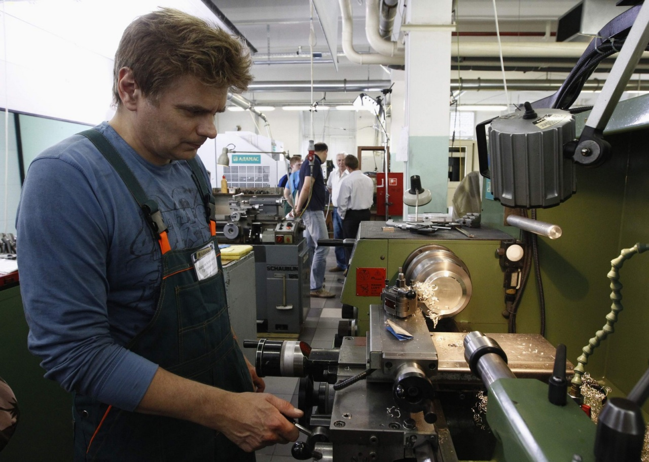 An employee operates a turning machine while working on medals for the 2014 Winter Olympic Games in Sochi, at the Adamas jewellery factory in Moscow