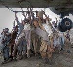 Пострадавшие при наводнении цепляются за боковины армейского вертолета, прибывшего распределить гуманитарную помощь. 7 августа, Пакистан, Muzaffargarh district, фото Adrees Latif  Marooned flood victims looking to escape grab the side bars of a hovering