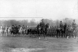 Император Николай II верхом на коне, императрица Александра Федоровна в коляске и сопровождающие их лица объезжают войска перед началом парада.