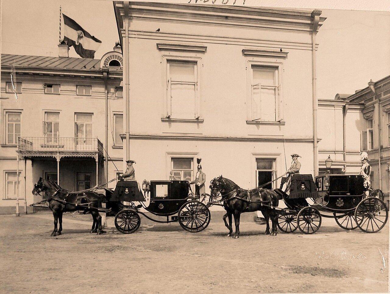 Кареты, запряженные парами лошадей, с кучерами и форейторами, подготовленные для участников торжественной коронации, на территории Кремля