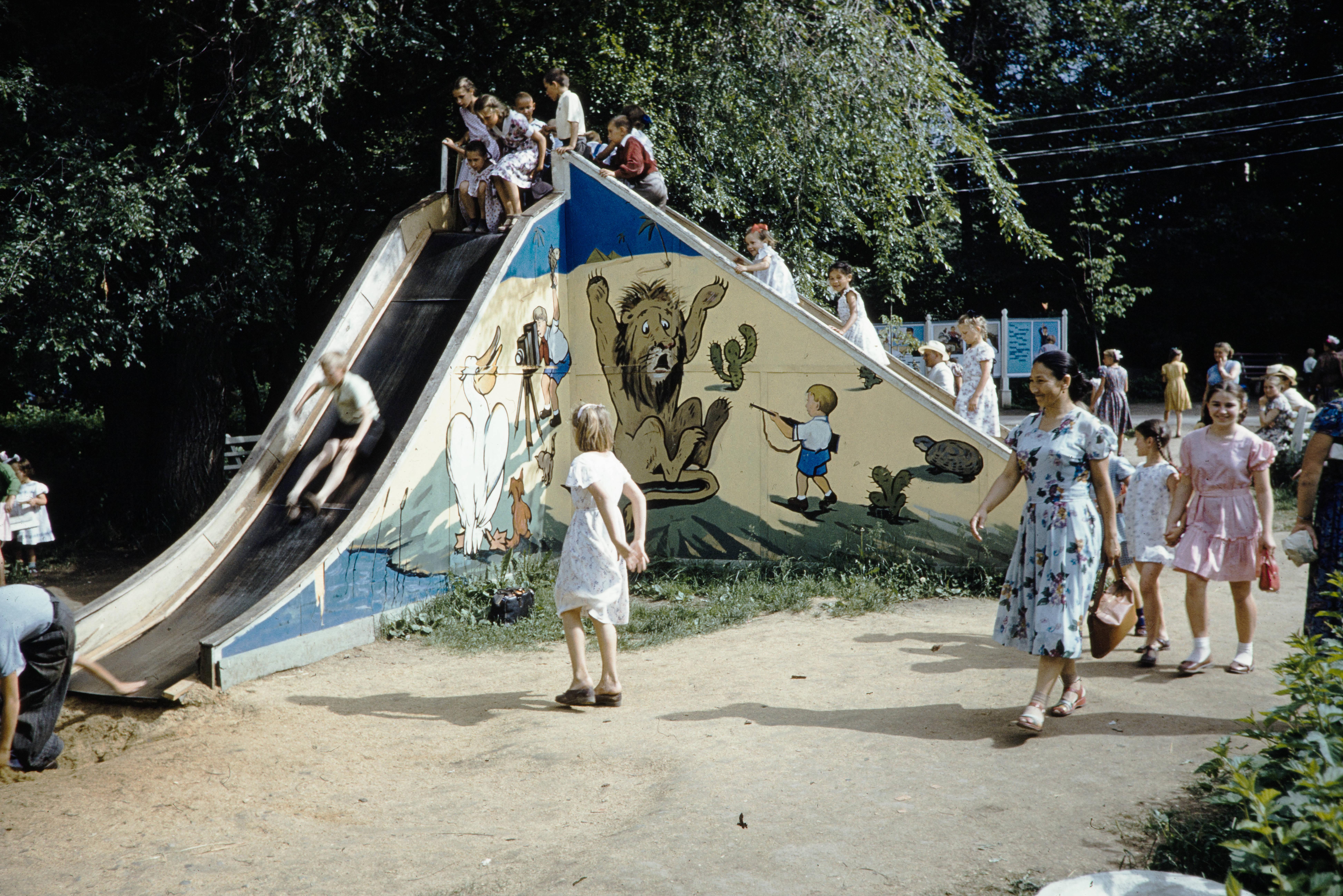 Дети катаются на горке в парке