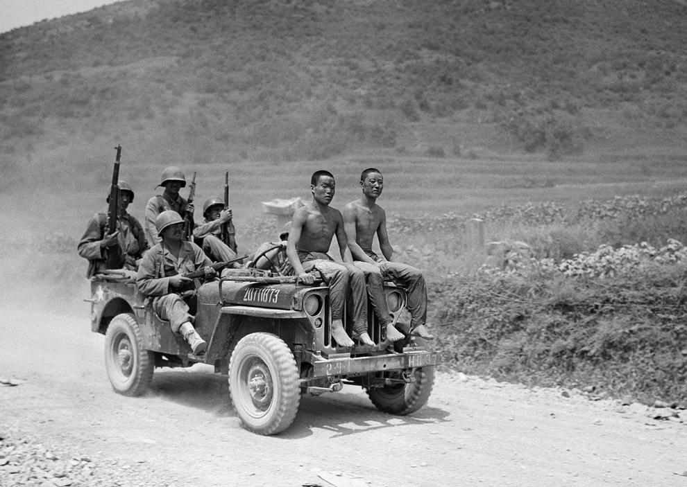 Солдаты везут двух северокорейских пленных, захваченных во время битвы за Йонсан, 2 сентября 1950 года. (AP Photo).jpg