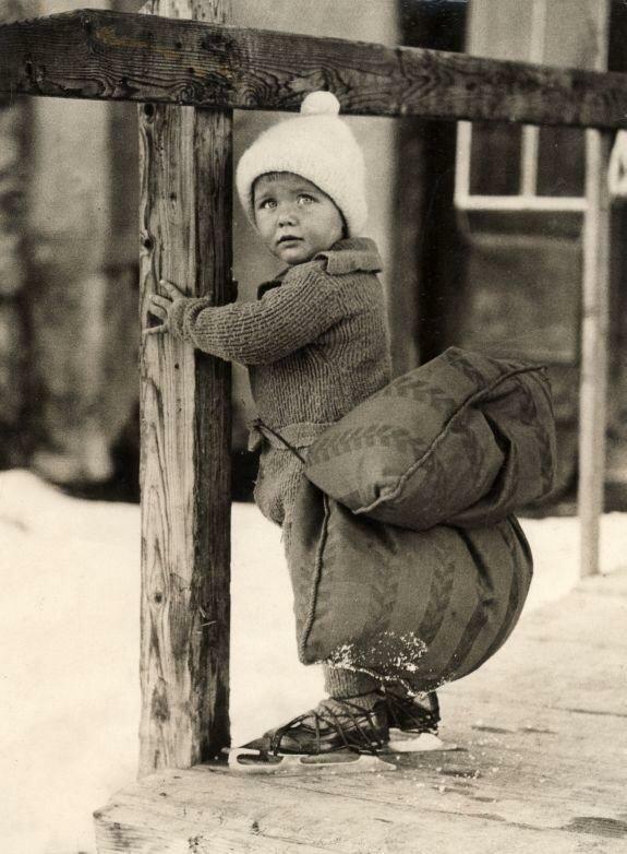 Jongetje met ijsmuts heeft een kussen onder zijn achterste gebonden gekregen om het vallen op het ijs tijdens het schaatsen te verzachten. Nederland, 1933.