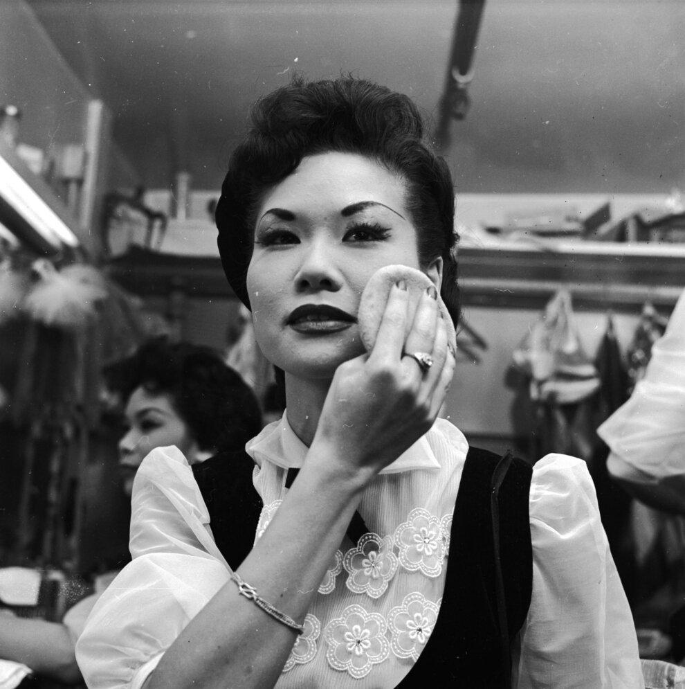 Хористка в ночном клубе Запретного города добавляет последние штрихи к своему макияжу.