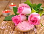 Roses, sea salt and candles on a brown table