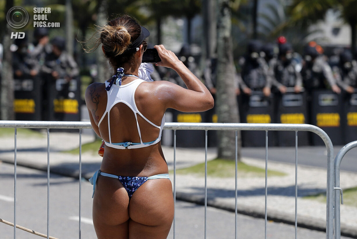 A resident takes a picture of National Force soldiers on Barra da Tijuca beach near Hotel Windsor, where the auction for Libra offshore oilfield will take place, in Rio de Janeiro