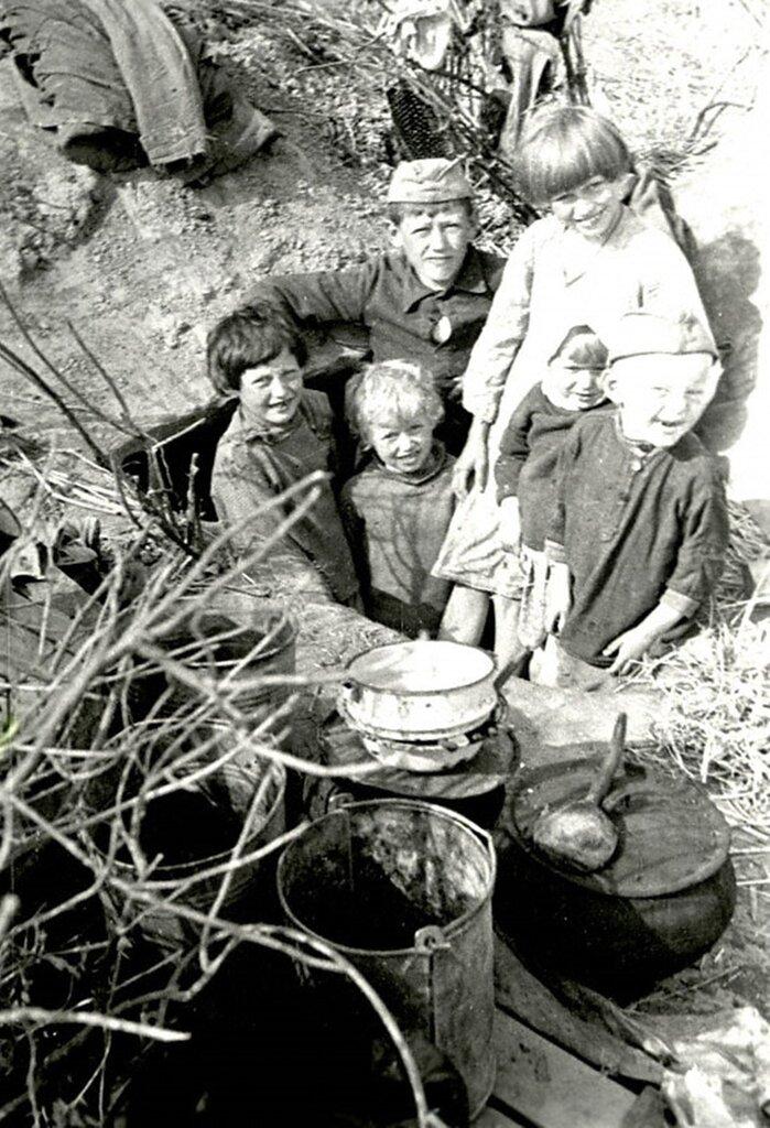 Дети колхозников одной из деревень Калининской области в лесу у землянки, где они жили в дни оккупации. 1942 г. Калининская область.