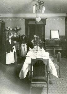 Официанты у стола, накрытого на три человека.