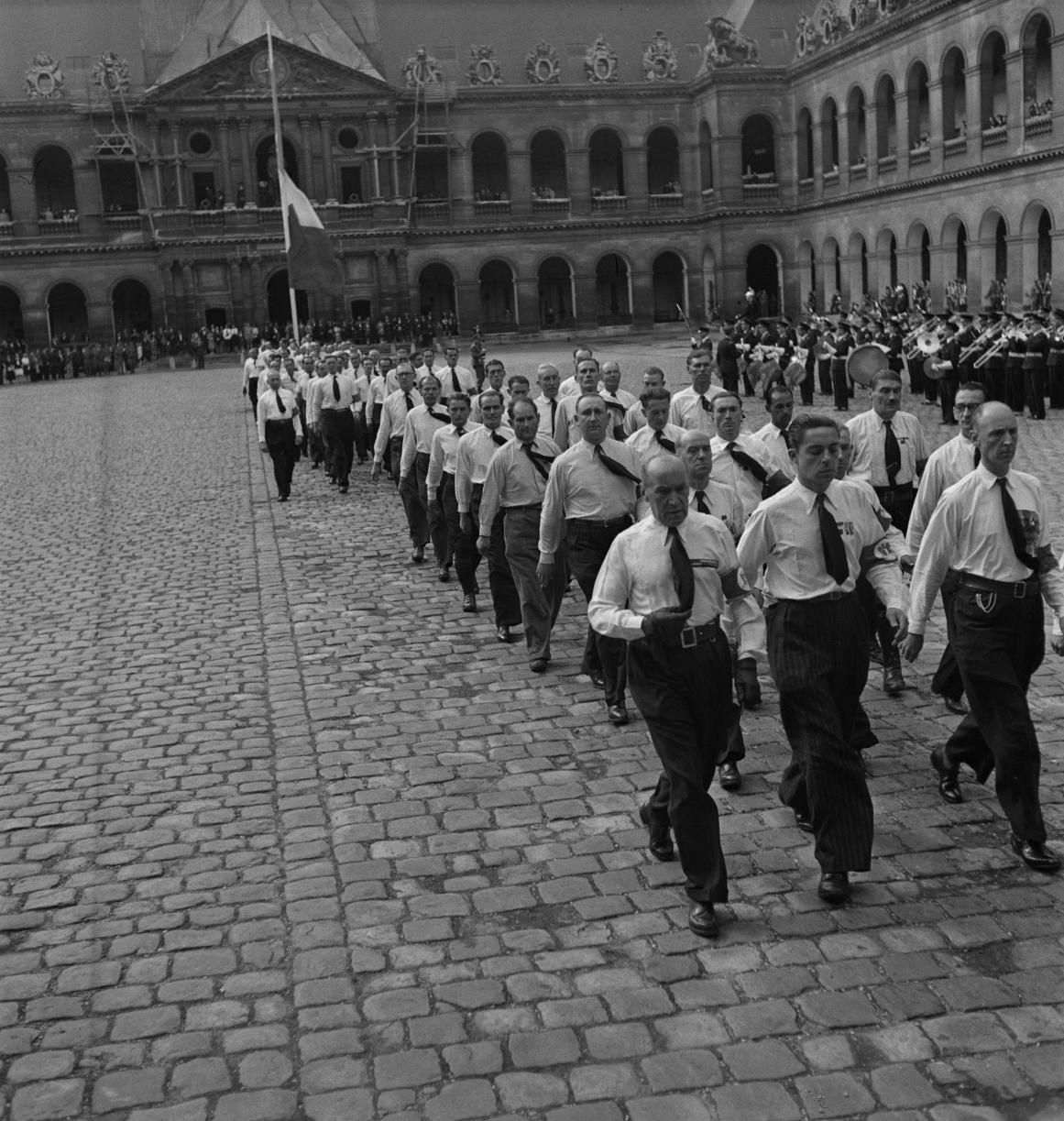 42. Затем под исполнение музыкантами из ВВС Полк Самбры-и-Мааса добровольцы проходят перед трибуной. Возглавляет легионеров капитан Демессин