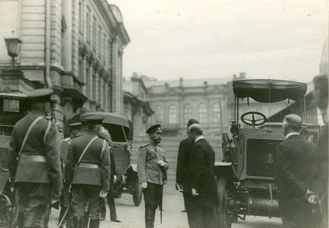 21. Император Николай II и сопровождающие его лица осматривают новую модель автомобиля у входа в выставочный зал