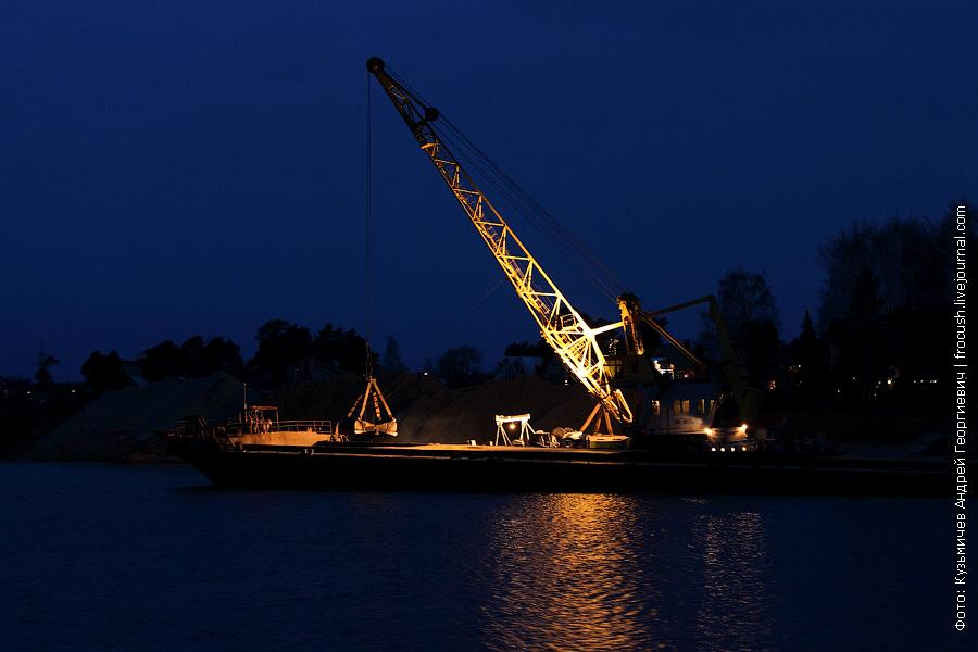 ночное фото плавкран разгружает баржу с песком на левом берегу Волги в Дубне