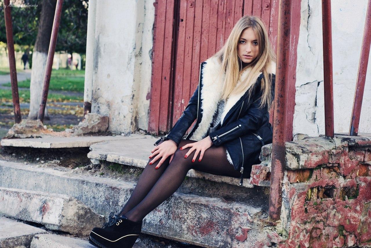Блондинка в кожаной  куртке и черных колготках