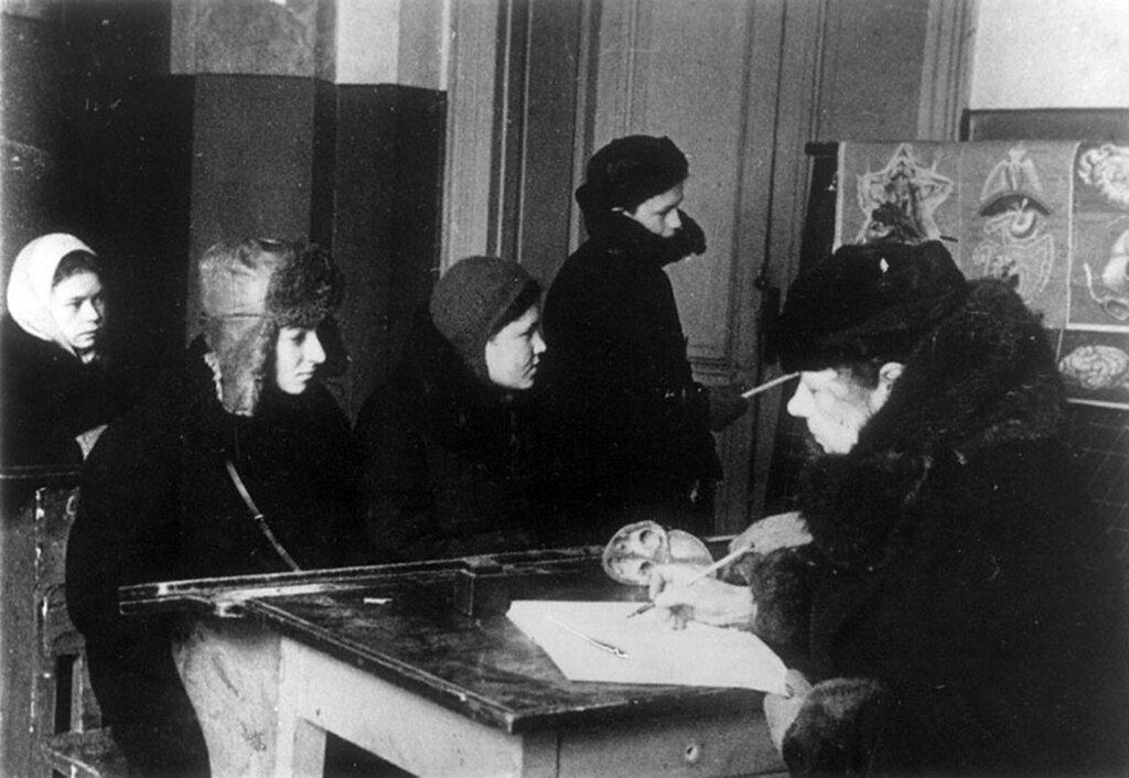 Урок естествознания в 7 классе школы № 239 Октябрьского района; справа – преподаватель А.И.Боконовец.  Апрель 1942 г. Ленинград.