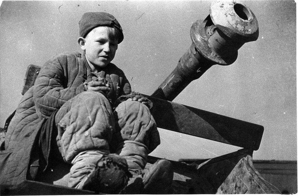 Советский подросток сидит у ствола брошенного при немецком отсуплении артиллерийского орудия.