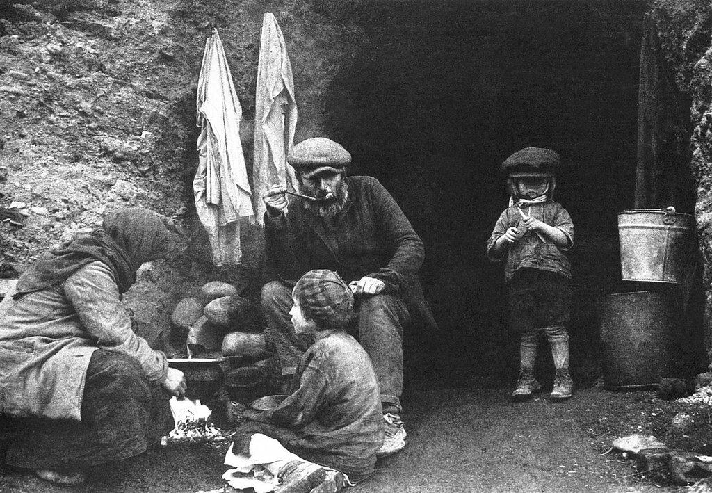 Советские беженцы за приготовлением еды у входа в землянку. Белоруссия. 1944 г.