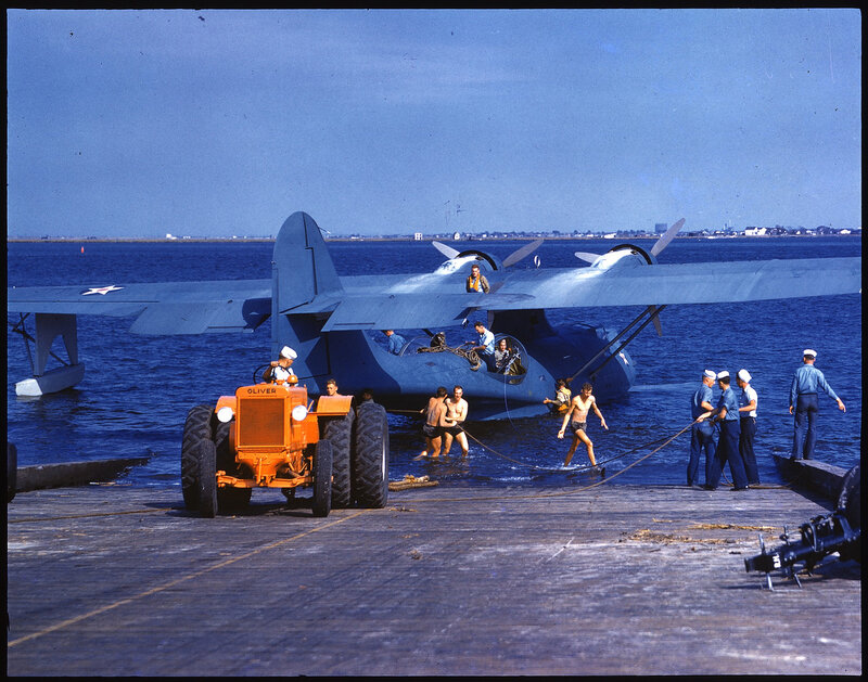 One-half right rear view of a U. S. Navy Consolidated PBY-5 Catalina being towed up a ramp and out of the water by an Oliver Corp. tractor, many servicemen are in the water and on and around the aircraft.