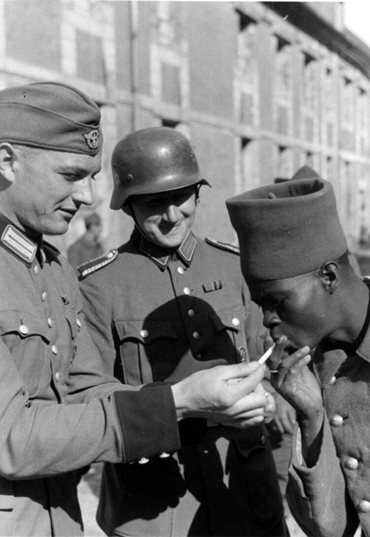 Немецкий солдат дает прикурить чернокожему военнопленному-французу. Май 1940