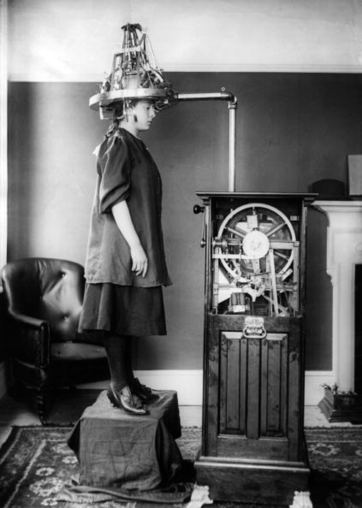 A woman whose head is attached to a machine which resembles a large hairdryer, but is in fact a Lavery Electric Automatic Phrenometer, for measuring brain activity.   (Photo by Topical Press Agency/Getty Images)