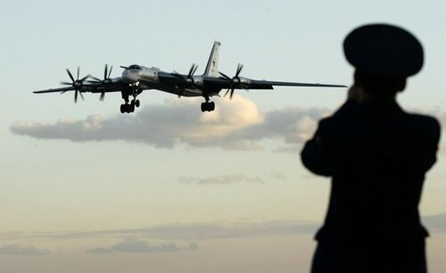 A Russian officer takes a picture of a TU-95 bomber, or Bear, at a military airbase in Engels