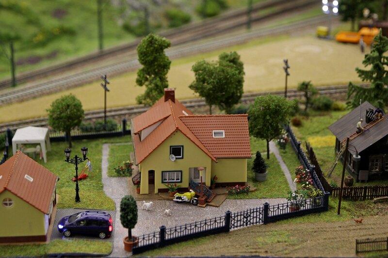 Гранд макет: богатый коттедж в деревне с выложенными камнем дорожками, подстригаемым газонокосилкой газоном, машиной, мотороллером и пуделем. И серая развалюха по соседству.