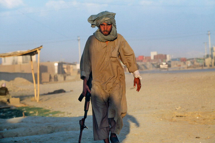 Sec3_11_41: May, 1997 A Taliban soldier walks away from heavy rooftop gunfire after his colleague was shot and mortally wounded. The Taliban were unaware they had been pulled into a massive trap by the Uzbek militia and suffered nearly 800 killed after tw