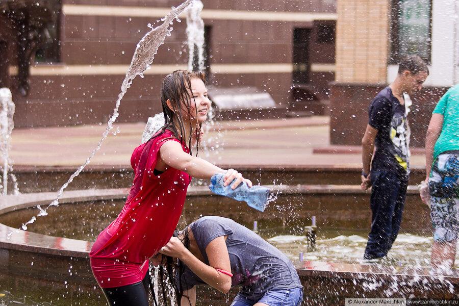 Девушка в мокрой одежде плескает водой из пластиковой бутылки