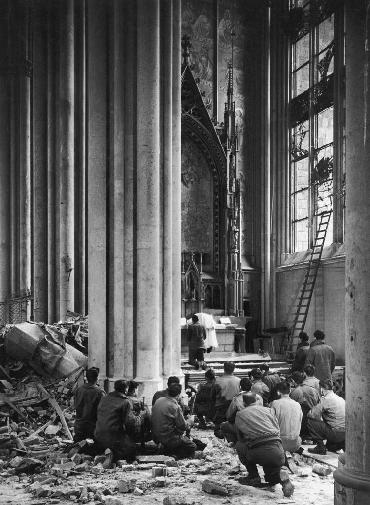 4/1945 American soldiers w. rifles kneeling to pray amidst bombing rubble in the main body of Cologne Cathedral as an Army chaplain holds first mass since it bombing on Mar. 2. Cologne Germany
