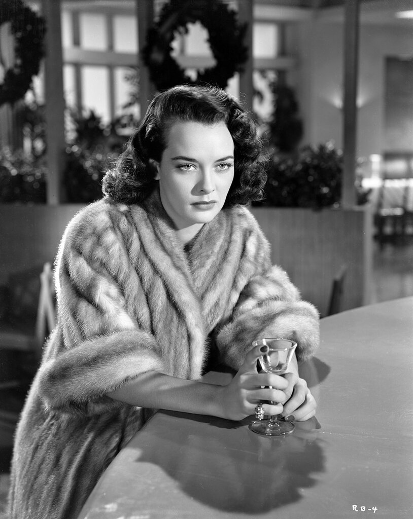 Joan Dixon has a drink in Roadblock (1951)
