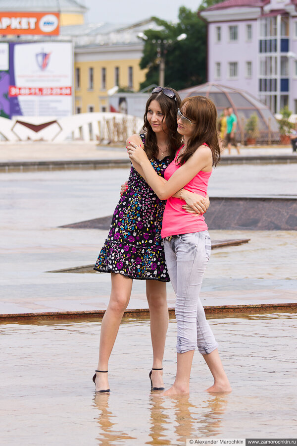 Две девушки позируют у фонтана
