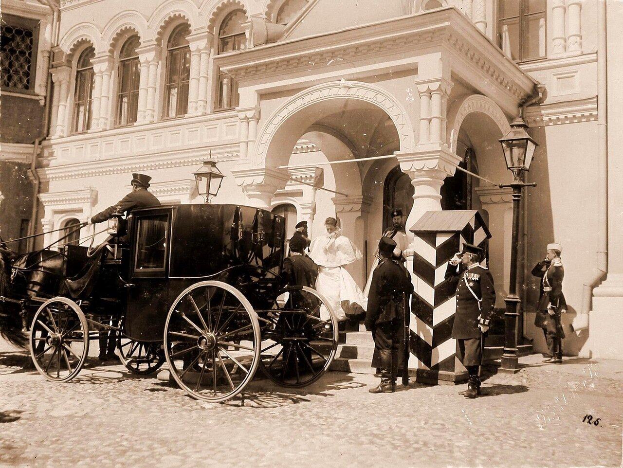 Императрица Александра Фёдоровна, император Николай II (за ней) направляются к карете из палат Чудова монастыря в Кремле в дни коронационных торжеств