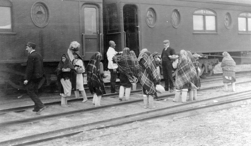 Pueblo women walk on railroad tracks carrying basins of items for sale to train passengers. 1905