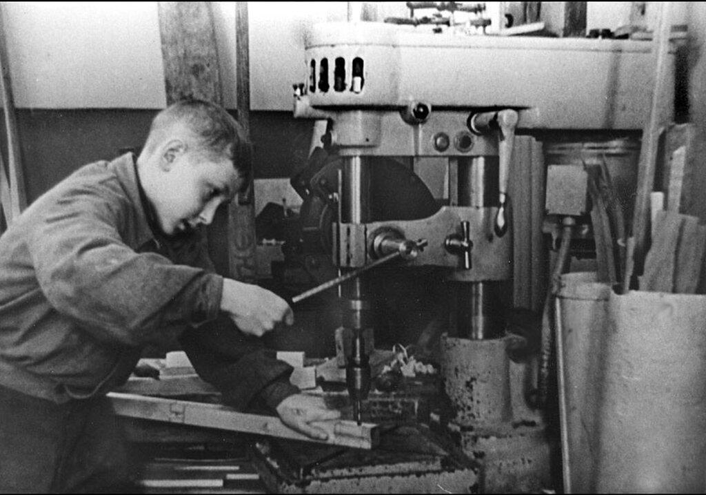 Подросток, работающий на сверлильном станке на оборонном заводе.