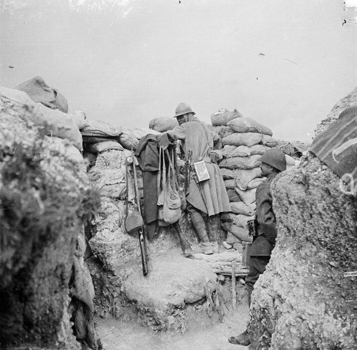 Sur la butte dite du Lorrain, un soldat senegalais monte la garde dans un poste d'observation. Vetu d'une capote d'hiver et d'une couverture, ce tirailleur possede a sa hanche gauche un coupe-coupe reglementaire des troupes coloniales.