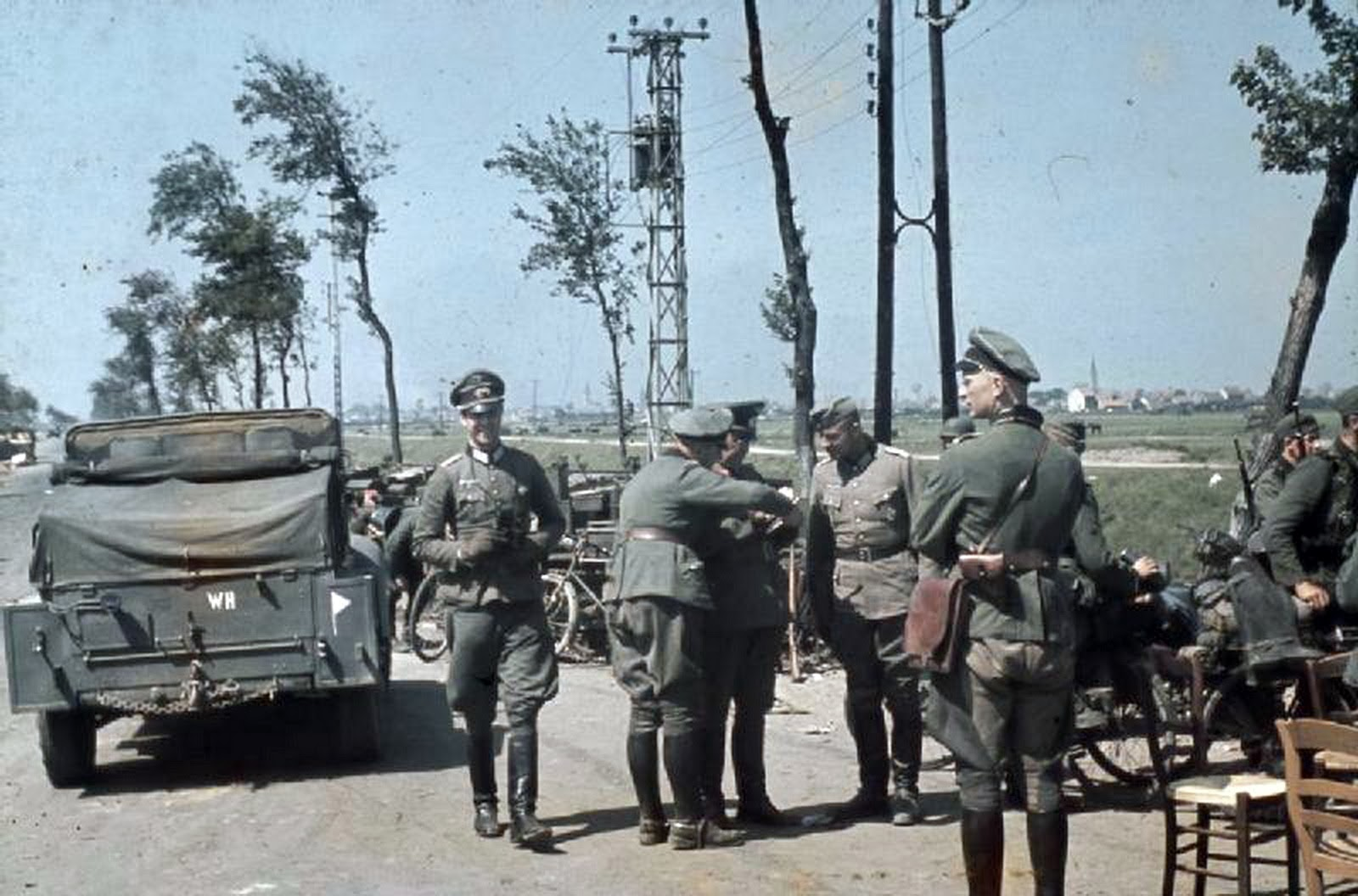 outskirts of Dunkirk, German officers confer by their vehicles at the roadside.jpg