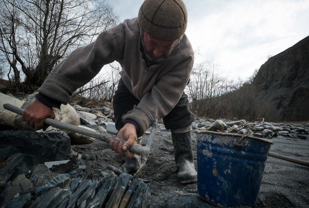 Я сперва не понял, зачем он набирает в ведро пластинчатые камни, пока не начался процесс очистк