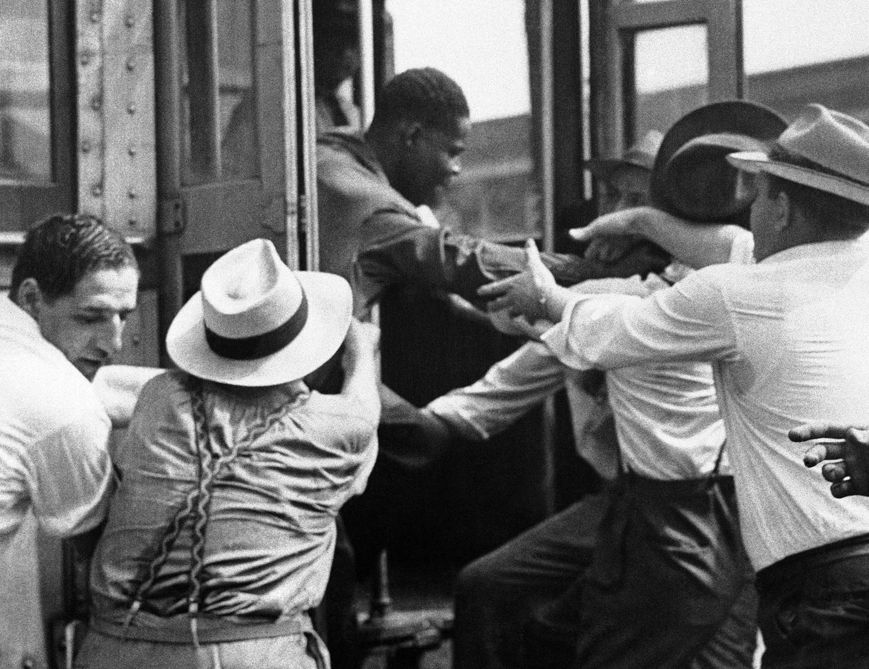 1943. 21 июня. Люди вышвыривают негров из трамвая в центре Детройта. Столкновения продолжаются на улицах города. Военное правление в городе была введено с целью остановить бунт