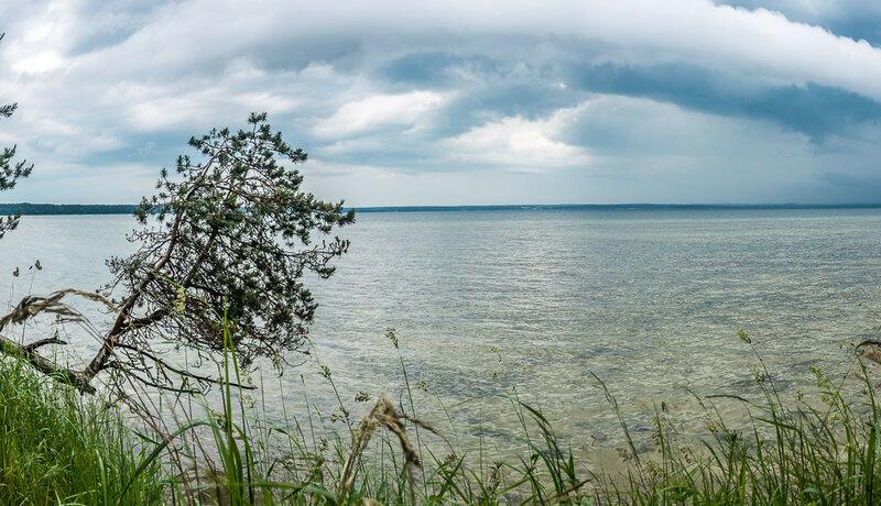 На озере неспокойно. Периодически проносятся тучи и поливают дождём.