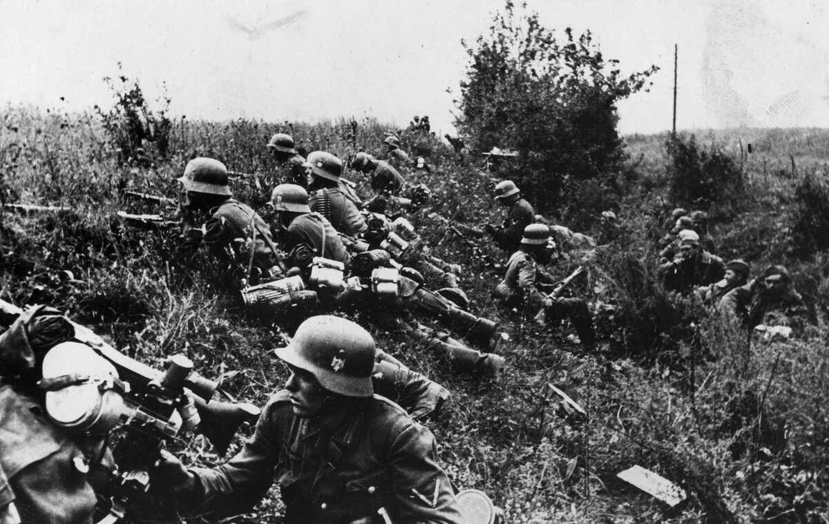 1941. Немецкие солдаты на позиции. За ними в канаве русские военнопленные
