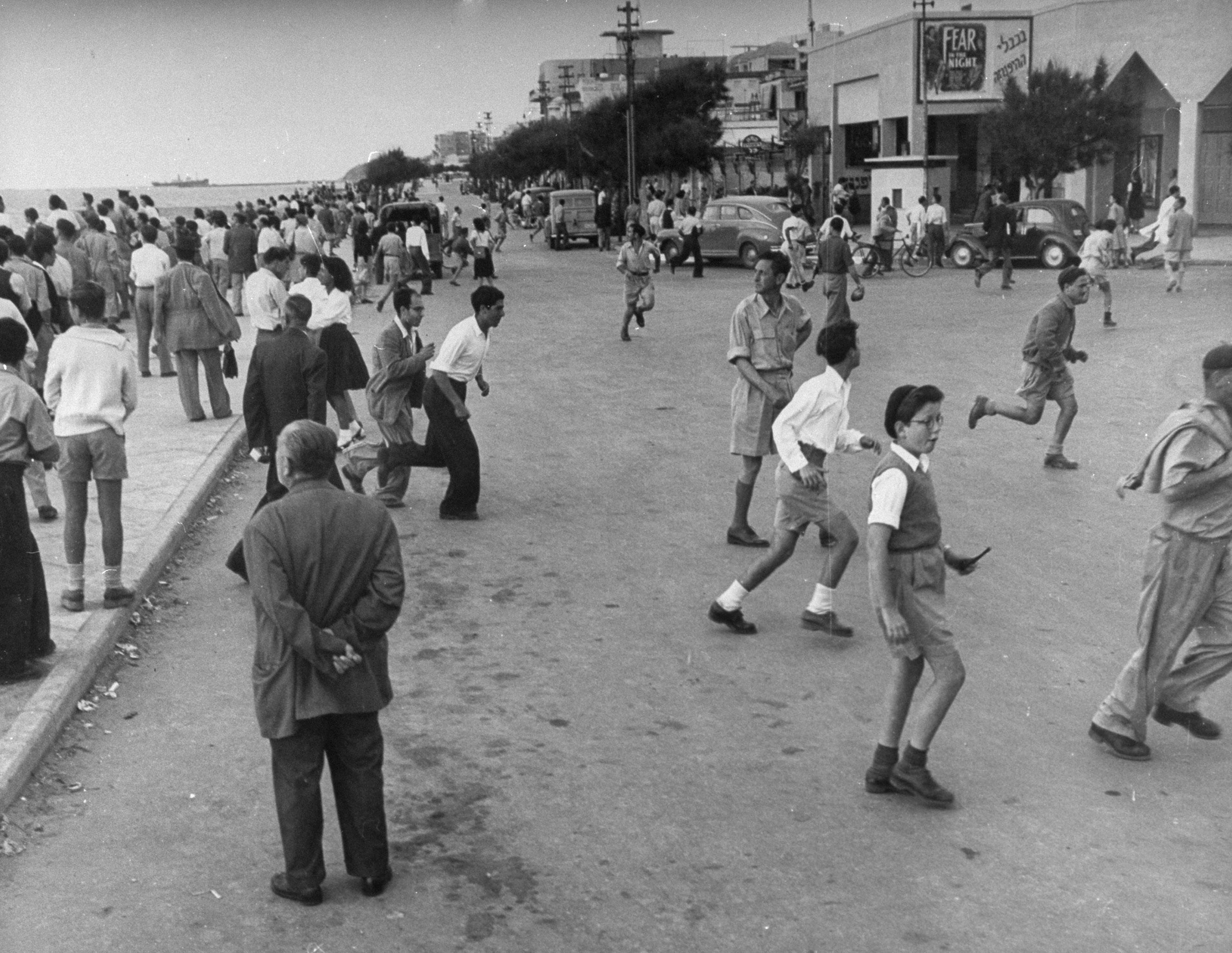 Люди бегут с набережной в Тель-Авиве во время воздушного налета. 15 мая