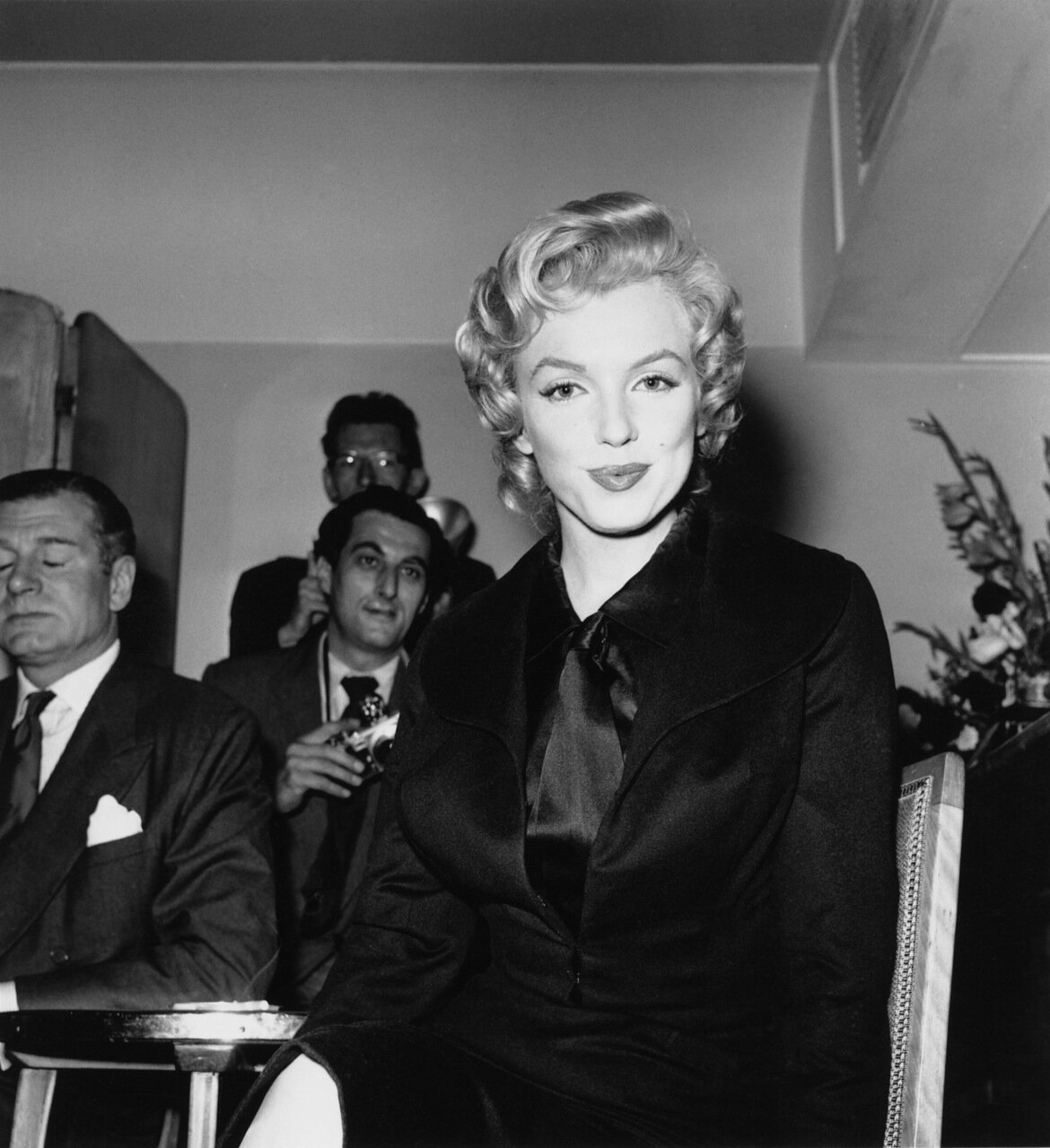 American actress Marilyn Monroe (1926 - 1962) at a press conference at the Savoy Hotel, London, July 1956. Monroe is in England to film 'The Prince and the Showgirl' with English actor and director Laurence Olivier (1907 - 1989, far left). (Photo by Harry