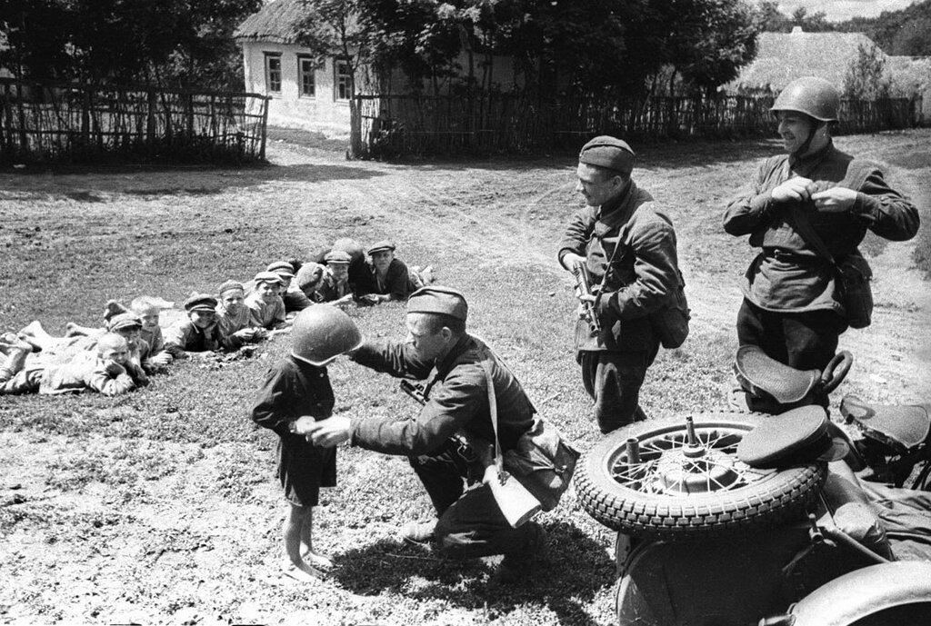 Солдаты 51-го отдельного мотоциклетного батальона 22-го танкового корпуса 38-й армии Юго-Западного фронта с советскими детьми. 1942 г.