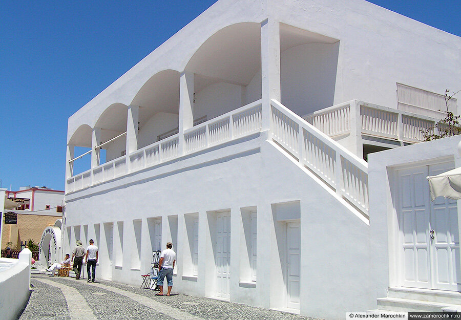 Белое здание с верандной в городе Фира на острове Санторини