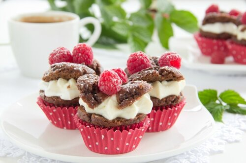 Chocolate muffins with raspberries and cream.