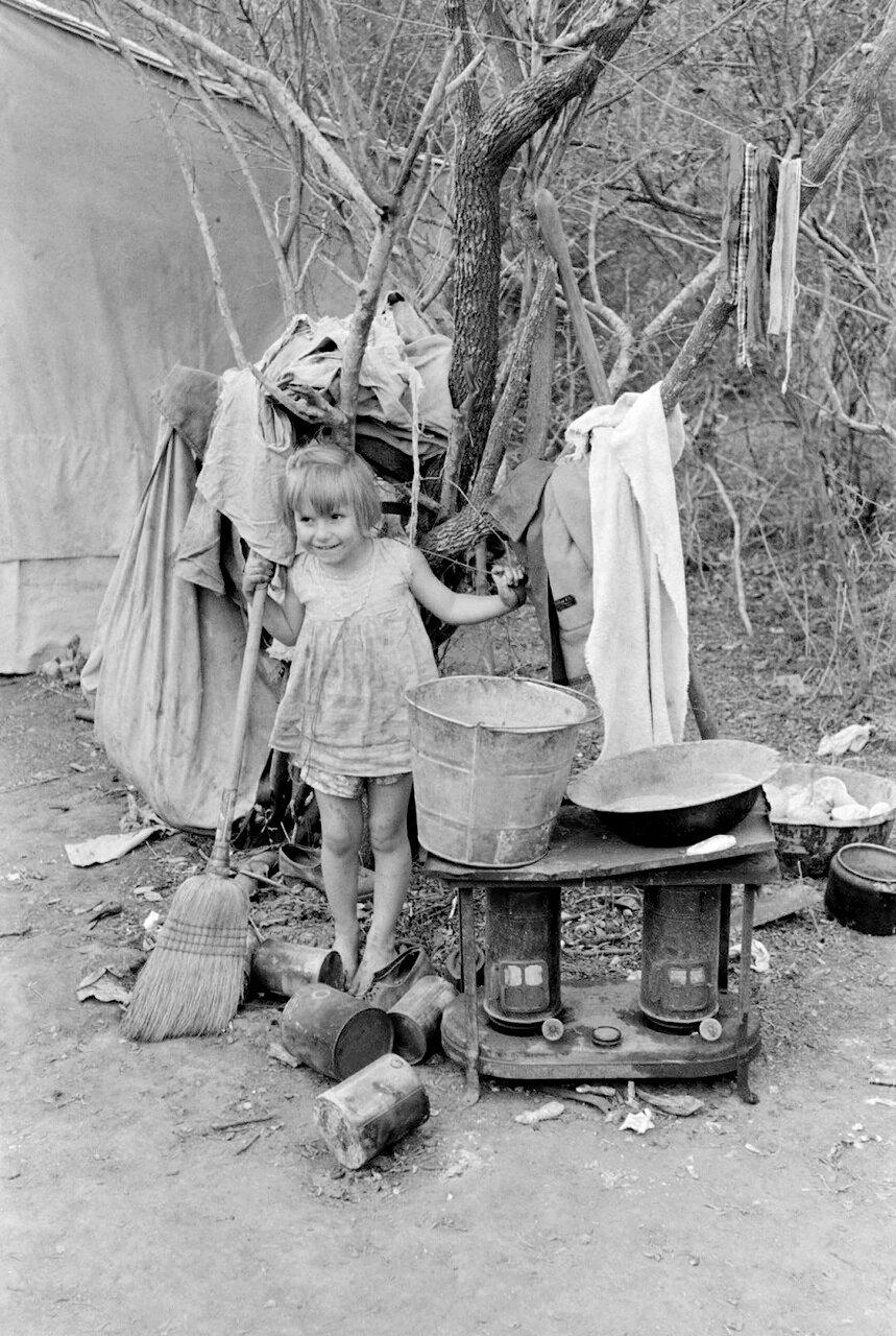 Наружная печь, умывальник и другой хозяйственный инвентарь семьи сезонных рабочих возле Харлингена, Техас, 1939