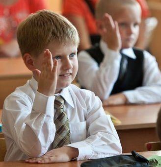 Первоклассник на уроке тянет руку отвечать