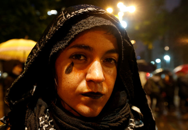 A woman with a tear painted on her cheek participates in a demonstration against gender violence in