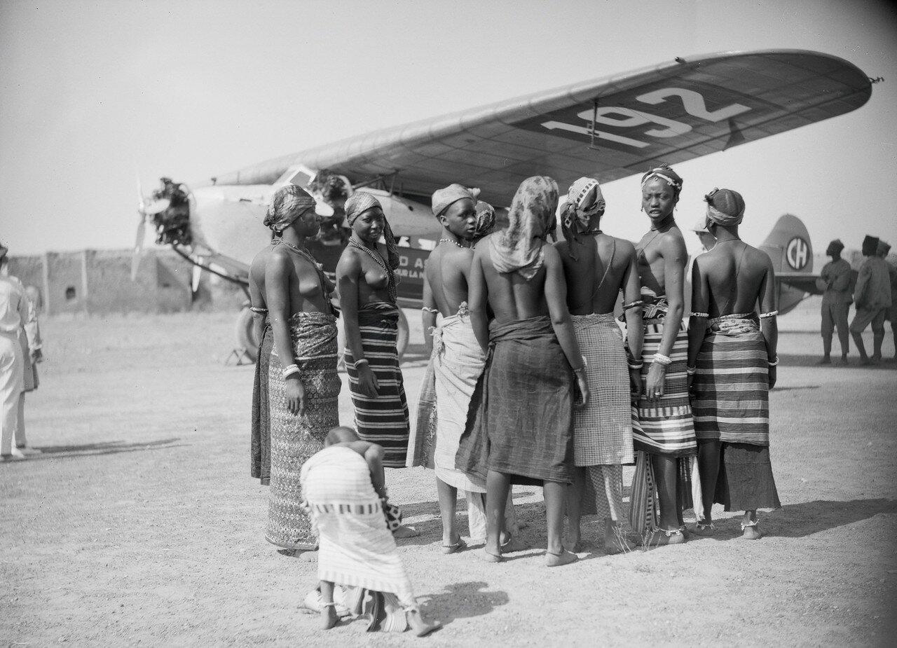 С напряженным пристальным вниманием деревенские красавицы следят за запуском нашего самолета