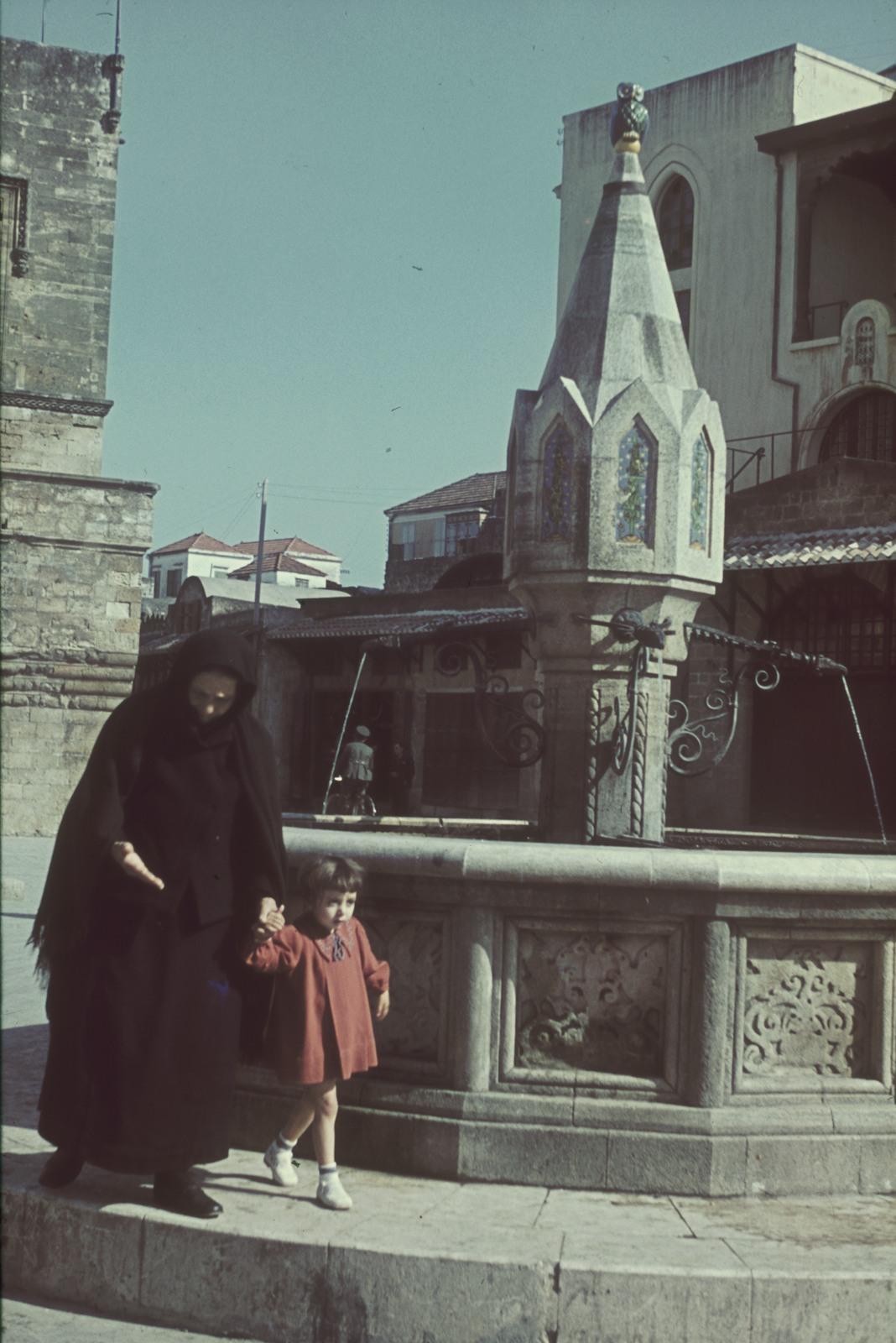 Старый город. Старая женщина с ребенком воле фонтана