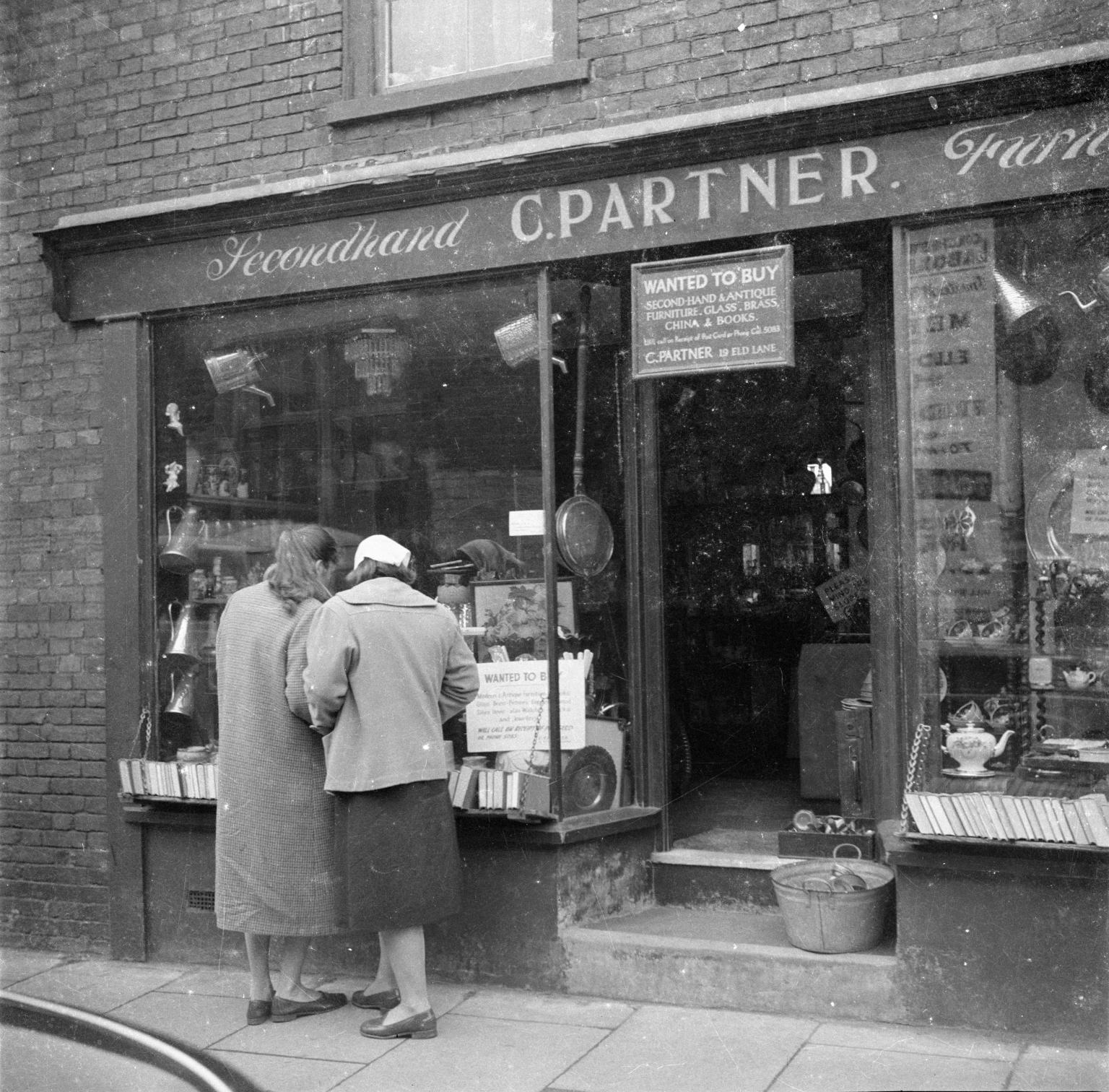 Женщины, разглядывающие витрину магазина